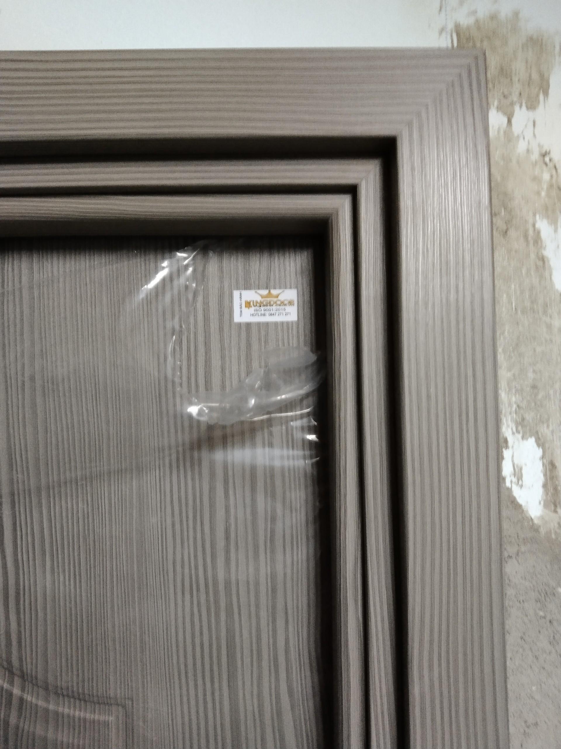 Cửa nhựa gỗ composite có tem bảo hành được gắn trên đầu cánh cửa